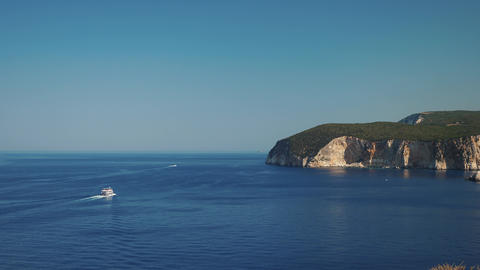Sea shore in Greece with high cliffs and a boat passing on the sea Footage