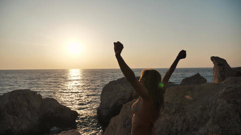Tourist girl on the top of the cliff celebrating victory at the dusk near the sea Live Action