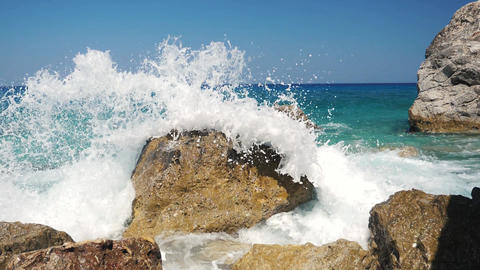 Sea wave hitting the rock on the beach in slow motion. Water drops in slow motion Live Action