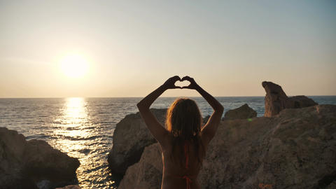 Girl in front of the sea showing a hearth shape with her hands Footage