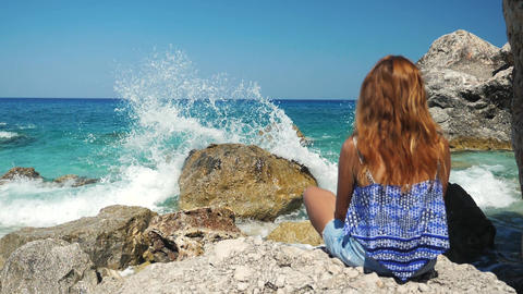 Girl in front of a sea wave near rocks recorded in slow motion Live Action