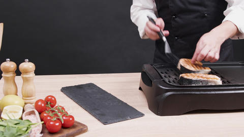 Cheef cooking a fresh salmon fillet on electric frying pan Live Action
