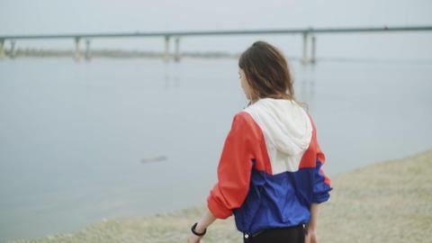 Beautiful young woman walking near the river. Young woman walking along the Live Action
