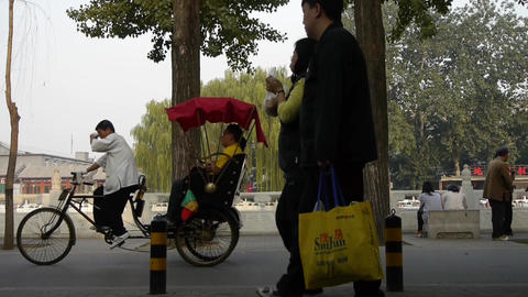 Tricycle carrying tourists sightseeing in Beijing's tree... Stock Video Footage