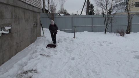 The girl with a shovel removes snow Live Action