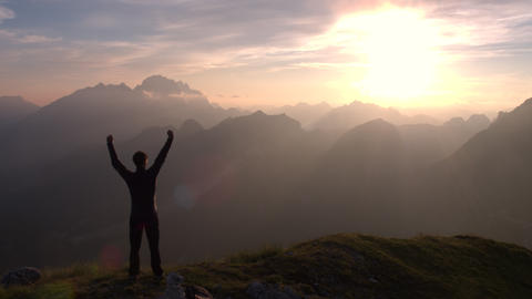 Aerial - Behind silhouette of a man standing on top of the mountain Footage