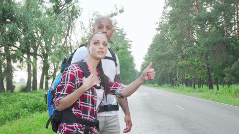Beautiful multiracial couple hitchhiking on countryside road Live Action