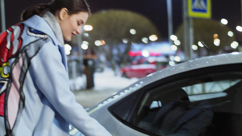 happy lady in elegant coat gets into car in evening street Footage