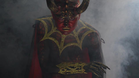 Lots of smoke, devil with red skin and red eyes, with horns on the head Live Action