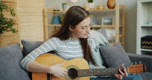 Young lady in glasses playing the guitar at home enjoying music and leisure time Footage