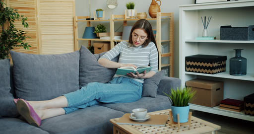 Attractive young woman reading interesting book enjoying literature at home Live Action
