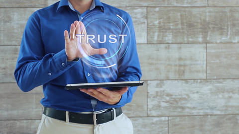 Man uses hologram with text Trust Live Action