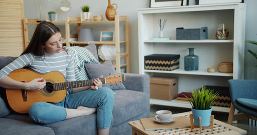 Pretty young woman playing the guitar in cozy apartment having fun alone Footage