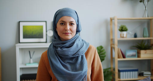 Portrait of mixed race girl in hijab looking at camera with serious face Live Action