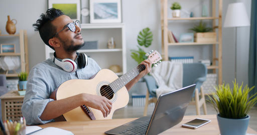 African American guy playing the guitar and using laptop indoors at home Live Action