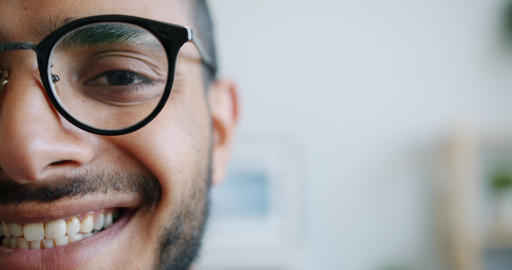 Close-up portrait of half of male face looking at camera smiling indoors Live Action