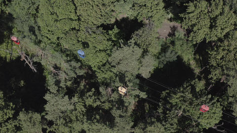 Aerial drone shot of a cable car moving over a green forest in summer on a synny Live Action