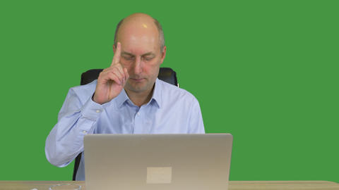 Businessman working on laptop in office on green background. Focused businessman Live Action