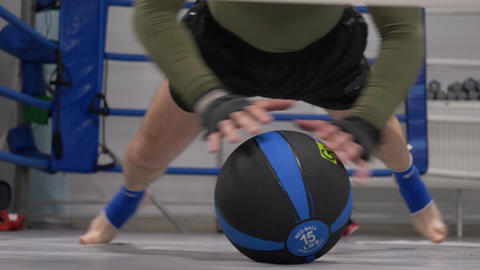 Fitness man training push up exercise with med ball in gym. Close up athlete man Live Action