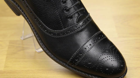 Approaching, black classic men's shoes standing on a wooden floor. Men's fashion Footage