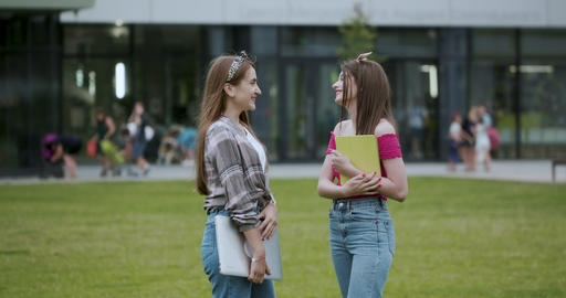 Two female college students while standing outdoors big urban building. Two teen Footage