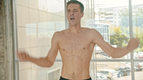 An athletic man training in the studio with an effort - repeats movements with a Footage