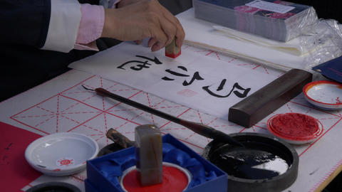 Slow motion, close-up shot of hand using a stamp to write traditional Japanese Footage