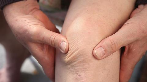 Man massaging a sore knee closeup Footage