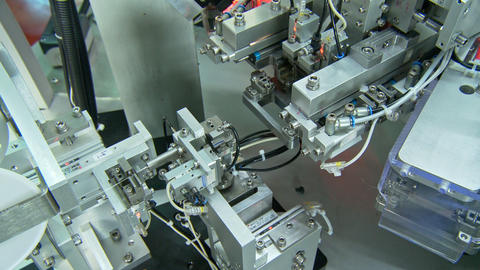 Close up on industrial production line for small parts, robotic arms Live Action