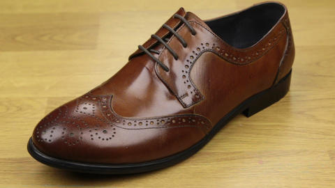 Approaching, brown classic men's shoes standing on a wooden floor. Men's fashion Footage