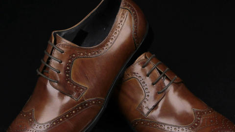 Approaching, pair of brown classic men's shoes standing on on a black background Live Action