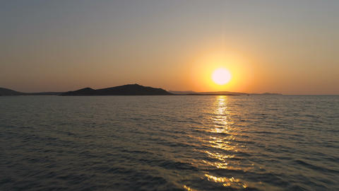 Golden sunset over sea and island, sun path reflecting from sea surface Live Action