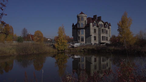 Huge grey dwelling house with nice pond in front of it located in country side Live Action