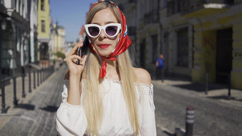 Portrait of cute young woman standing on the street talking by cellphone Live Action