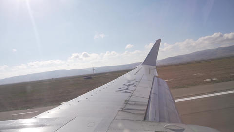 Nice view of wing of airplane flying above the clouds with blue sky Live Action