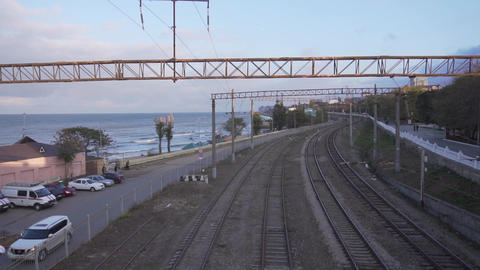 Camera moves showing old bridge over railways nearby coastline on sunny day Live Action