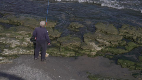 Old man in cap stands on rock shore and does fishing with fishing rod in hand Live Action