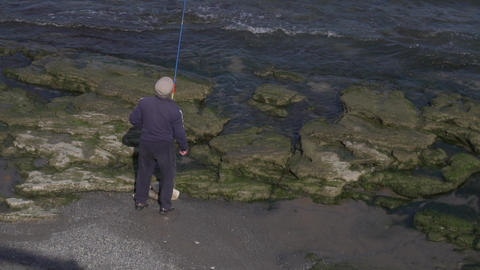 Older male in cap stands on rock shore and does fishing with fishing rod in hand Live Action