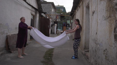 In narrow street two women hold ends of bed sheet and shake it together Live Action