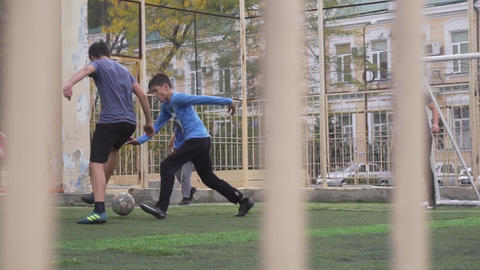 Energetic boys are playing football on mini football pitch with high fences Live Action