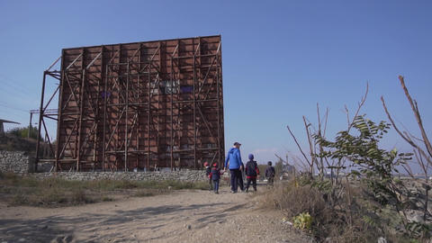 Male in blue jacket with a group of kids are walking around billboard structure Live Action