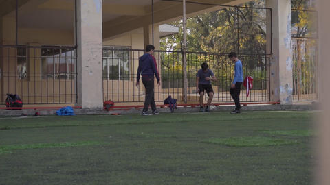 Boys are joyfully playing football on mini football pitch with high fences Live Action
