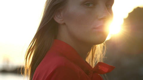 slow motion. close-up. face of a blonde with green eyes on a background of sunset sun rays Live Action