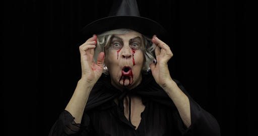 Old witch Halloween makeup. Elderly woman portrait with blood on her face Live Action