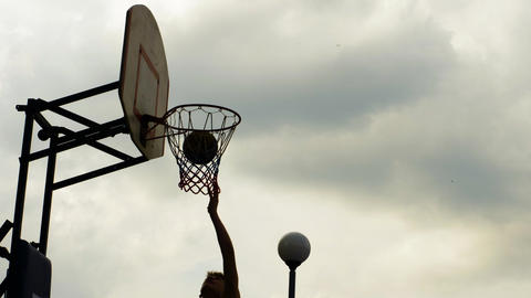 Basketball player throwing ball in hoop on sport ground. Athlete throwing ball Live Action