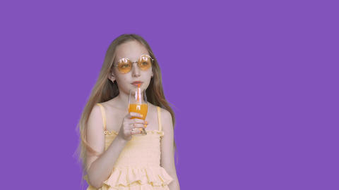 Teenager girl drinking orange juice from glass by straw on violet background Live Action