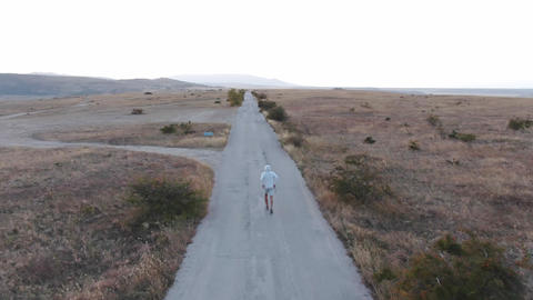 AERIAL: A man in a gray tracksuit runs along a road that runs through the hills Footage