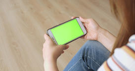 Young Woman Sitting On Floor Using Cellphone On Green Background At Home Live Action