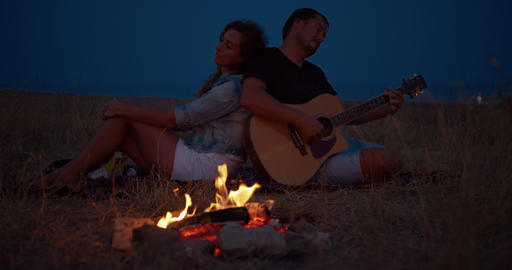 Young couple sitting near bonfire, man playing guitar. Romantic music and happy Footage