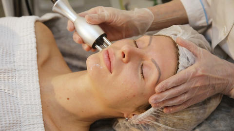 Young woman receiving electric facial massage Live Action